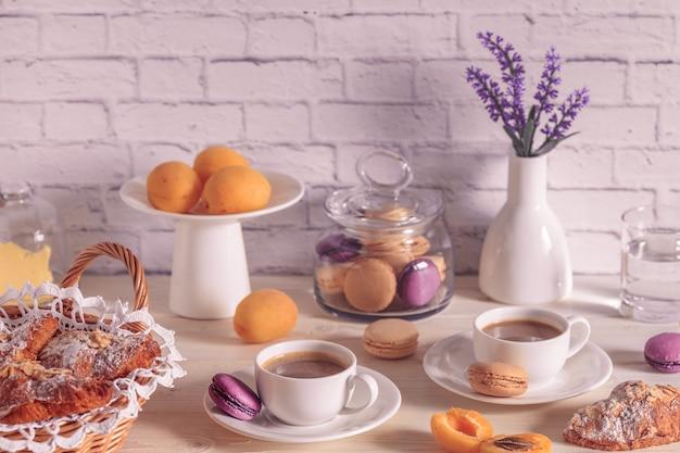 Café da manhã com vários macaroons, croissants e chocolate quente