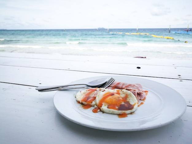Café da manhã com vista para o mar de fundo ovos fritos, salsicha, omelete simplesmente comida de café da manhã na mesa de madeira,
