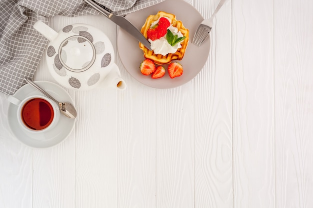 Café da manhã com waffles belgas em madeira branca