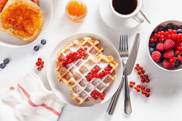 Café da manhã com waffles, torradas, bagas, geléia e café. vista do topo