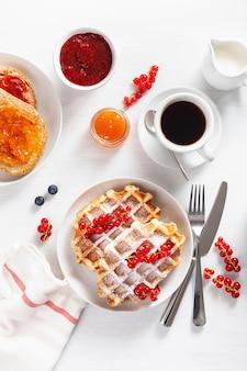 Café da manhã com waffles, torradas, frutas silvestres, geléia, chocolate e café. vista do topo