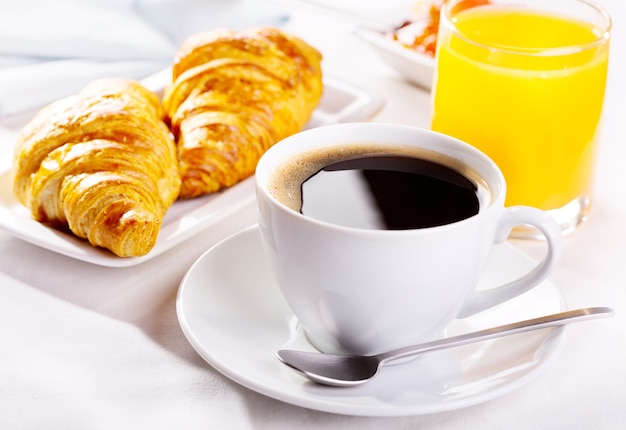 Café da manhã com xícara de café, croissants e suco de laranja