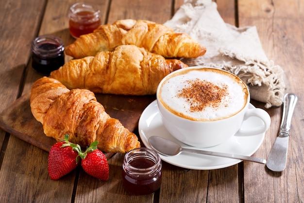 Café da manhã com xícara de cappuccino café com croissants na mesa de madeira