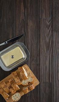 Café da manhã. composição com manteiga em uma manteiga e baguete em uma mesa de madeira