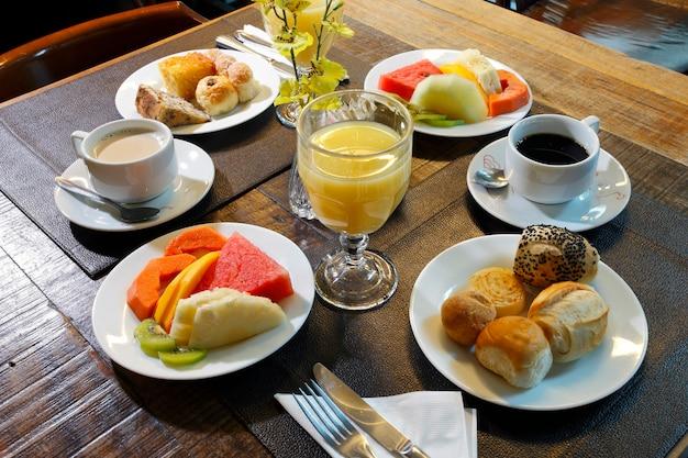 Café da manhã composto por frutas, suco de laranja, café, pão.