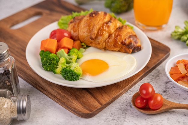 Café da manhã composto por pão, ovos fritos, brócolis, cenoura, tomate e alface em um prato branco.
