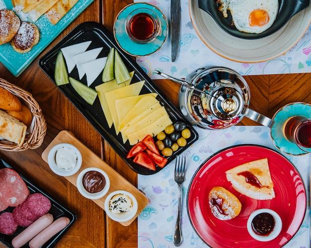 Café da manhã conjunto ovos queijo salsichas panquecas crepes azeitonas chá vista superior
