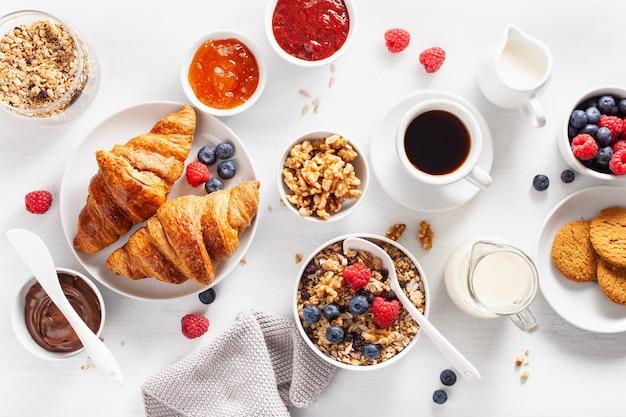 Café da manhã continental com croissant, geléia, chocolate e café. vista do topo