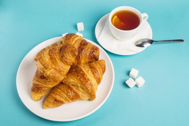Café da manhã continental com croissants dourados franceses e xícara de chá