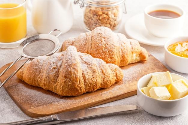 Café da manhã continental com croissants frescos, suco de laranja e café, foco seletivo.