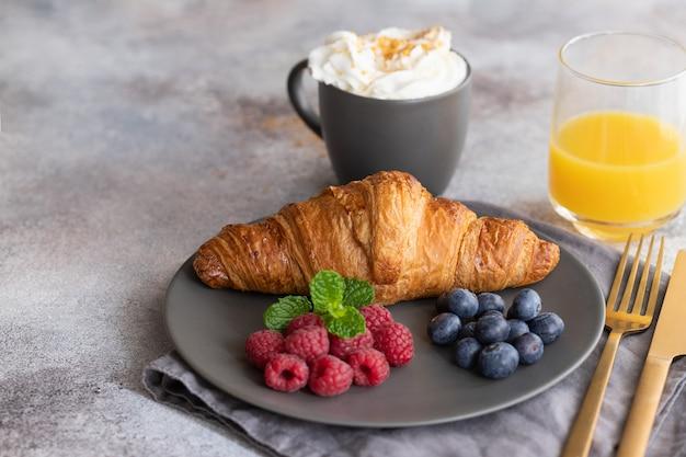 Café da manhã continental, croissant francês, café com leite, frutas e suco de laranja.