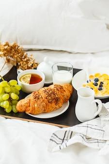 Café da manhã continental na cama. croissant, flocos de milho, chá, leite e frutas na bandeja preta.