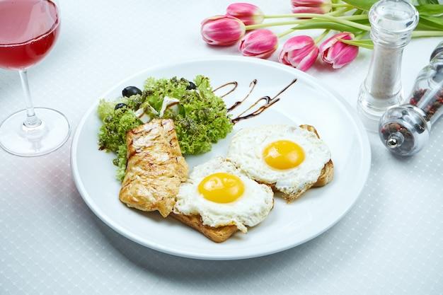 Café da manhã continental - torradas com ovos fritos, filé de frango grelhado, salada com queijo feta e azeitonas em um prato branco. vista superior, espaço de cópia