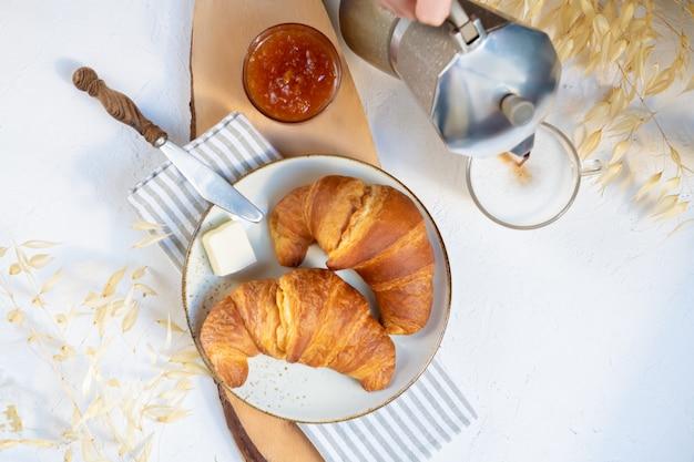 Café da manhã continental, uma xícara de café com leite, dois croissants, manteiga e geléia de laranja em uma placa de madeira, vista superior