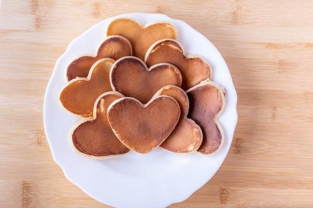 Café da manhã criativo do dia dos namorados. café da manhã romântico na cama. panqueca em forma de coração caseiro em um prato branco sobre um fundo de madeira