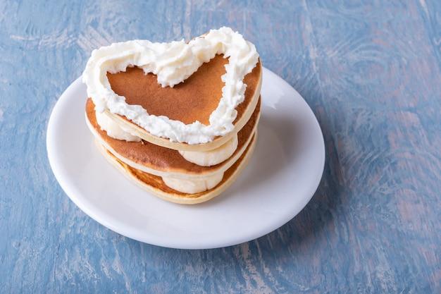 Café da manhã criativo do dia dos namorados. panqueca caseira em forma de coração com banana decorada com creme branco em um prato branco sobre uma mesa de madeira azul