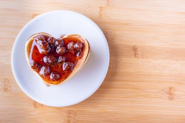 Café da manhã criativo. panquecas caseiras em forma de coração com geléia de baga em um prato branco sobre um fundo de madeira.