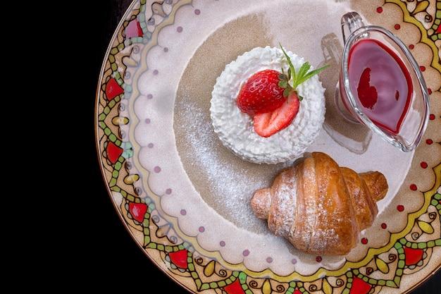Café da manhã. croissant com queijo cottage, morangos e geléia, em uma placa de cor, sobre um fundo preto. vista do topo