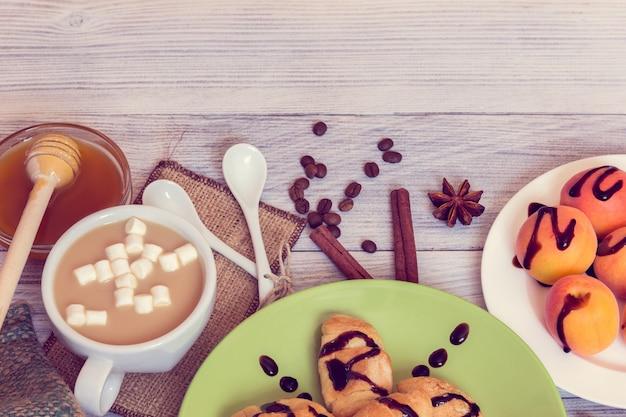 Café da manhã de café, croissants, damascos, mel, canela e anis