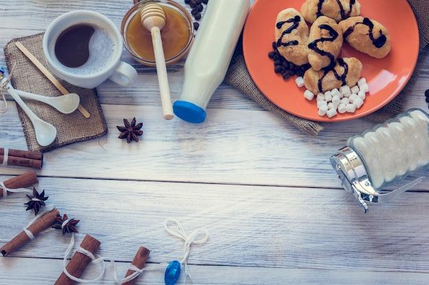 Café da manhã de café, croissants, leite, mel, açúcar, canela, anis