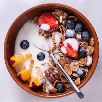 Café da manhã de cereais e frutas com iogurte em tigelas de barro sobre uma toalha de mesa branca