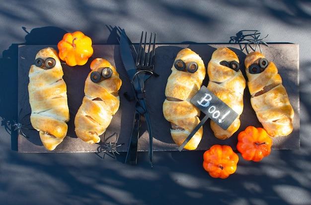 Café da manhã de comida de halloween. salsichas de massa em forma de múmias. comida festiva de halloween para crianças