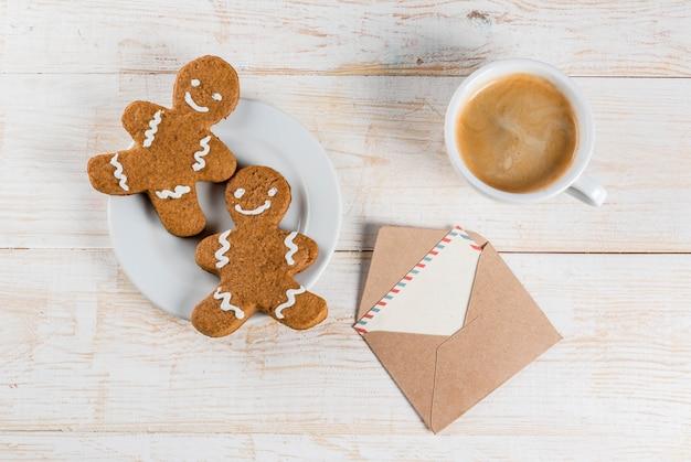 Café da manhã de natal, caneca de café com biscoitos de gengibre, com envelope com carta, na mesa de madeira branca, vista superior copyspace