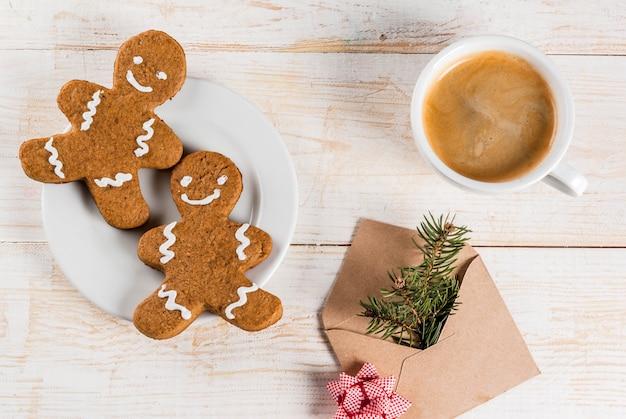 Café da manhã de natal, caneca de café com biscoitos de gengibre, com envelope com galho de árvore de natal, na mesa de madeira branca, vista superior copyspace