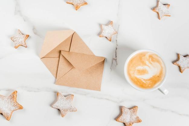 Café da manhã de natal, caneca de café com biscoitos de gengibre estrela, com envelopes, na mesa de madeira branca vista superior copyspace