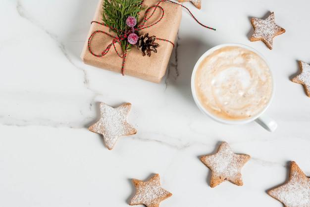 Café da manhã de natal, caneca de café com biscoitos de gengibre estrela, com presente de natal ou presente, na mesa de madeira branca vista superior copyspace