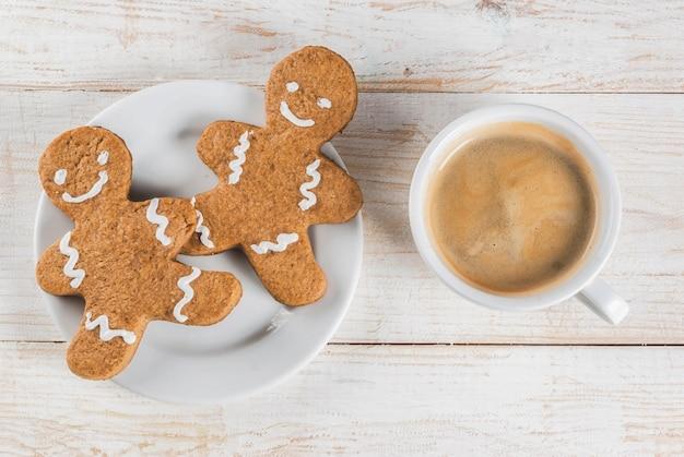 Café da manhã de natal, caneca de café com biscoitos de gengibre, na mesa de madeira branca vista superior copyspace