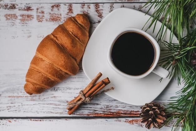 Café da manhã de natal com uma xícara de café, croissant, paus de canela