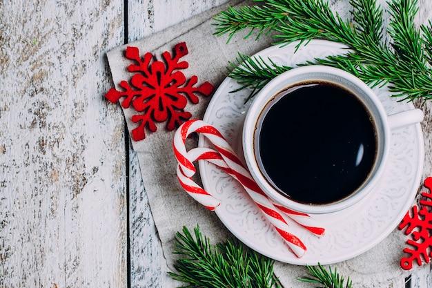 Café da manhã de natal. xícara de café, palitos de doces e brinquedos de decoração de férias