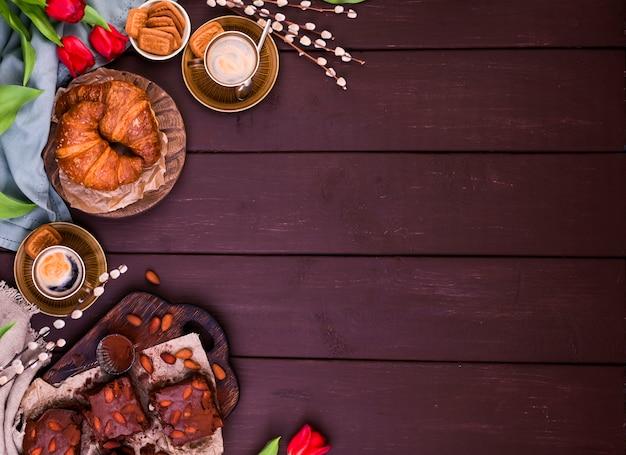 Café da manhã de páscoa com café expresso aromático fresco, croissants, ovos coloridos, tulipas vermelhas e salgueiro. café com bolos, flores em uma mesa de madeira. vista de cima. copie o espaço