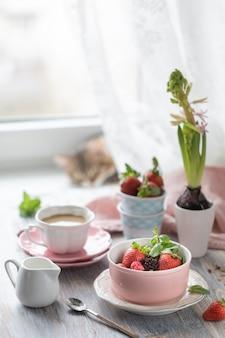 Café da manhã de primavera com granola e morangos frescos e lichia e flores sobre fundo de madeira.