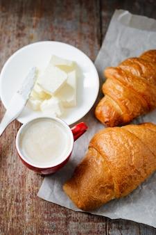 Café da manhã de uma xícara de café e croissants com manteiga