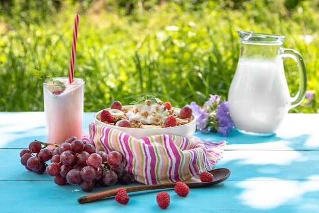 Café da manhã de verão ao ar livre com mingau com framboesas e uvas e delicioso iogurte com um canudo sobre uma mesa azul clara e um fundo de grama verde e uma jarra de leite.