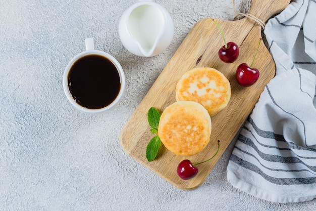 Café da manhã de verão com panquecas de queijo cottage, xícara de café preto, leite