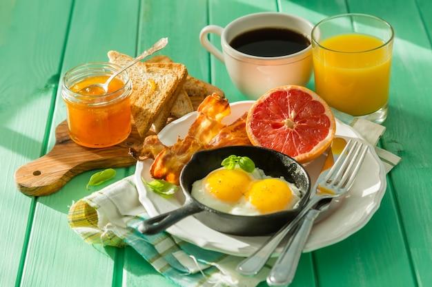 Café da manhã de verão - ovos, bacon, torradas, geléia, café, suco