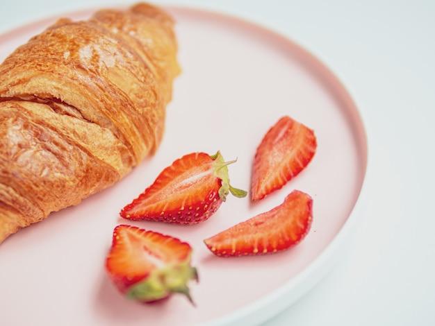 Café da manhã de verão. placa cor-de-rosa com croissants e morango. fechar-se