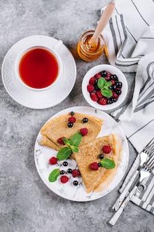 Café da manhã delicioso dos crepes no fundo concreto cinzento da tabela. panquecas com berry