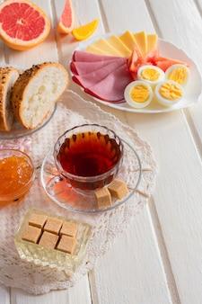 Café da manhã delicioso fresco com ovo cozido macio, queijo, pão fresco de presunto e xícara de café ou chá na luz de fundo de madeira.