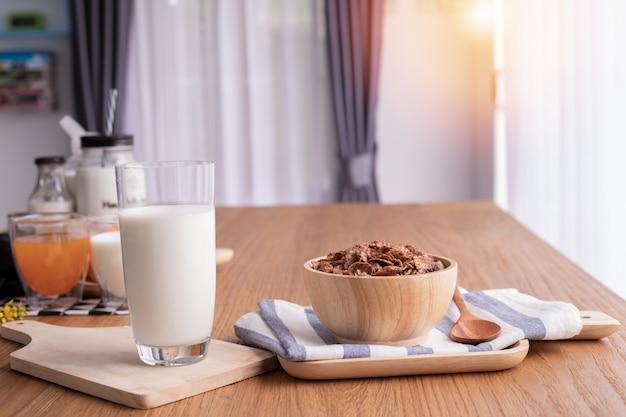 Café da manhã do cereal com vidro do leite na tabela de madeira na sala de visitas. tabela superior.