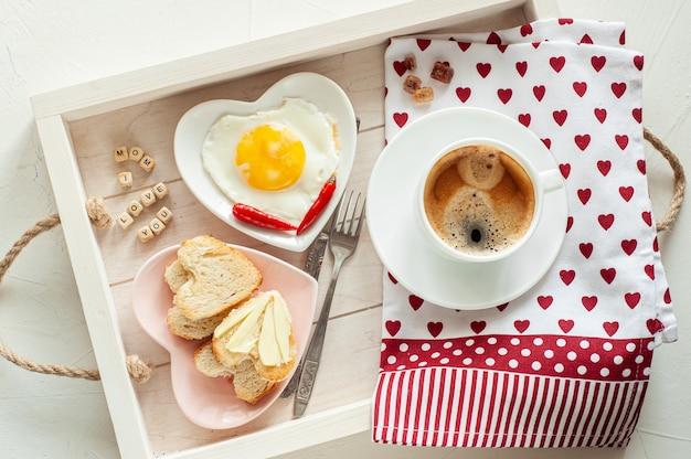Café da manhã do dia das mães. bandeja há uma xícara de café dois pratos de ovos mexidos e pão em forma de coração e a inscrição eu te amo mãe vista de cima