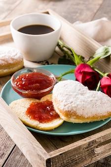 Café da manhã do dia dos namorados com café, pão em forma de coração, geléia de baga e rosas em uma bandeja