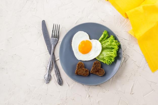 Café da manhã do dia dos namorados com ovos fritos em forma de coração, servido na placa cinza e guardanapo amarelo. disposição plana, vista superior