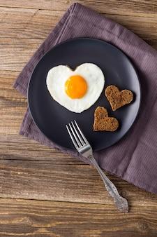 Café da manhã do dia dos namorados com ovos fritos em forma de coração, servido no prato cinza e guardanapo. disposição plana, vista superior