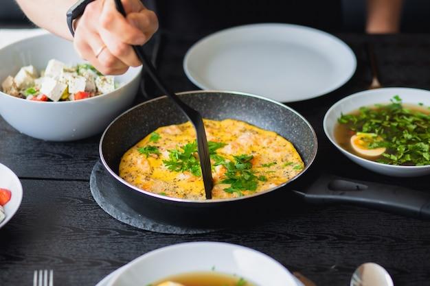 Café da manhã do lado de fora omelete de camarão no café da manhã omelete em uma frigideira no café da manhã almoço para um homem omelete frito com vegetais comida de verão na rua sopa de ovo comida regular caldo de dieta