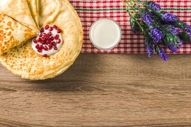 Café da manhã doce e saudável. deliciosas tradicionais panquecas finas de farinha de arroz, um copo de leite e lavanda na mesa de madeira.