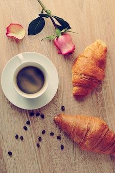 Café da manhã - dois croissants, café e rosa vermelha com pétalas rasgadas